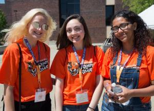 Three smiling student in the Student Union Plaza wearing Buffalo State T-shirts