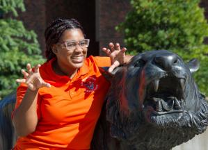 Smiling female student standing next to bengal statue making cat scratch gesture with hands.